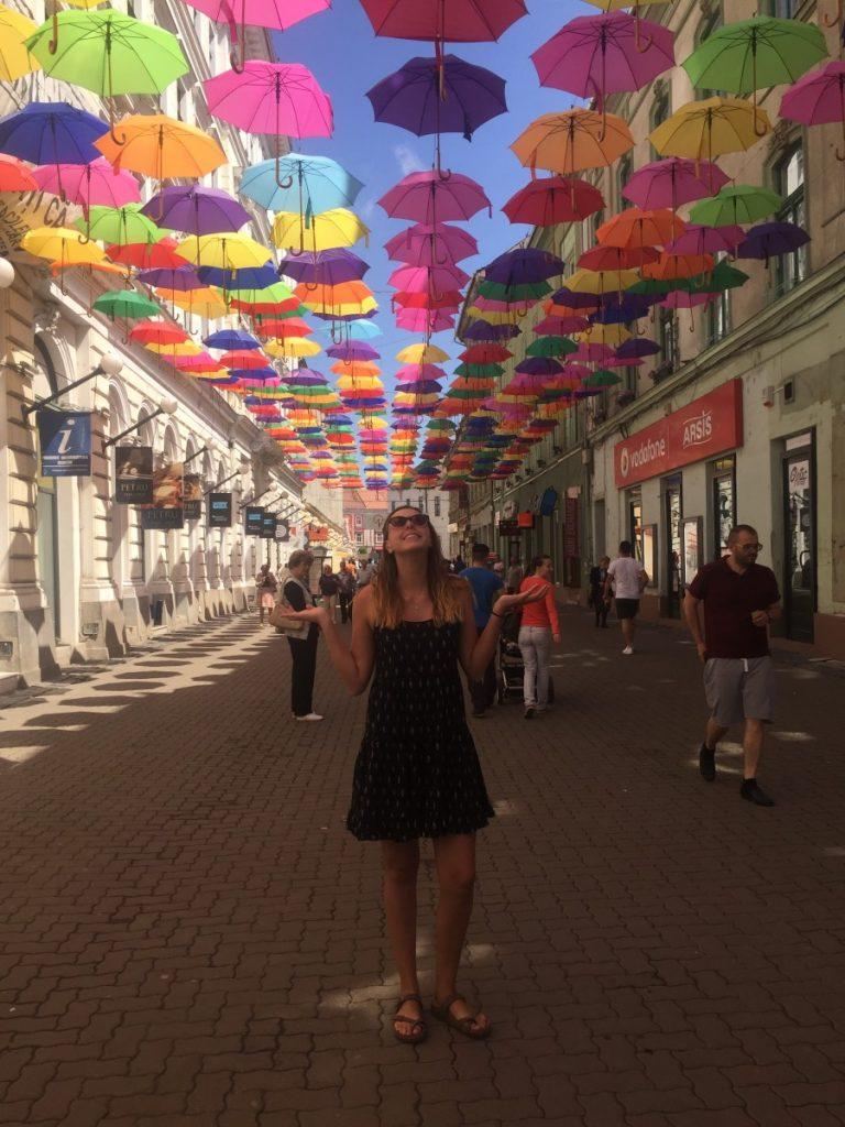 Emily standing under umbrellas