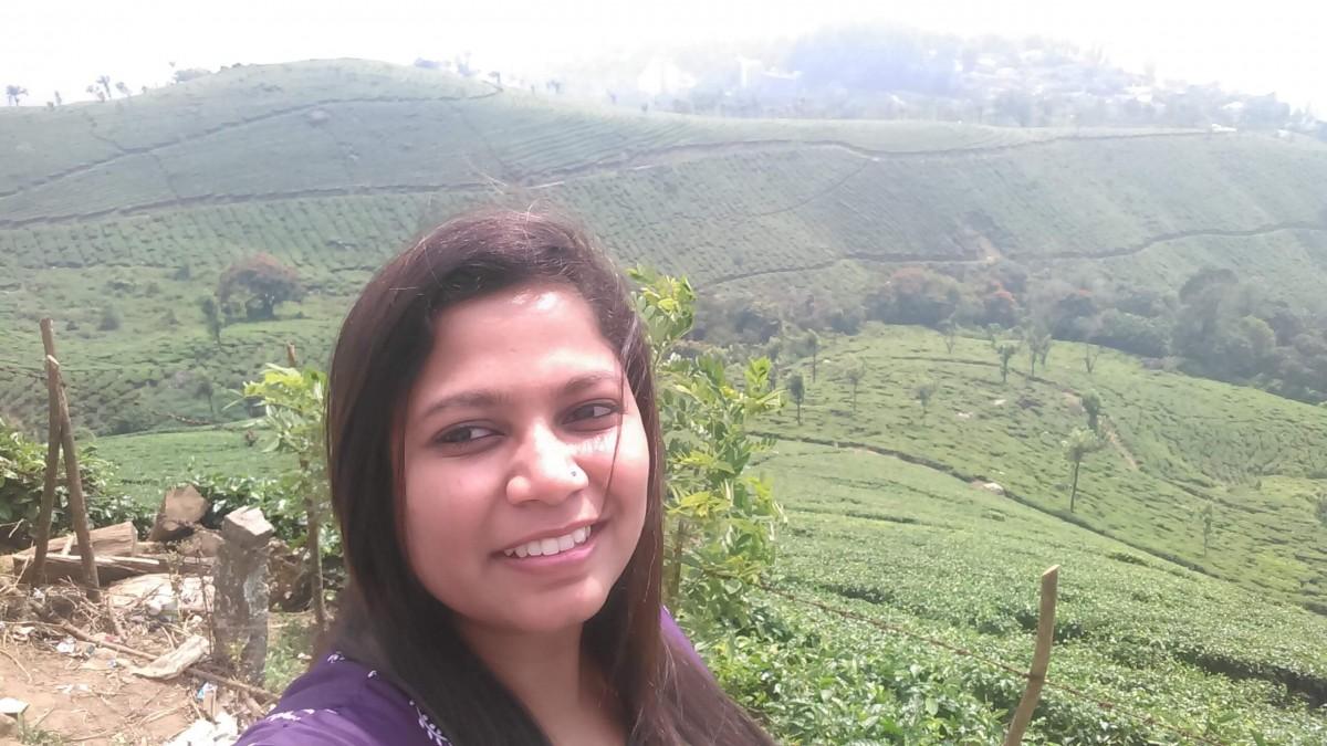 Bhavi posing over a plantation