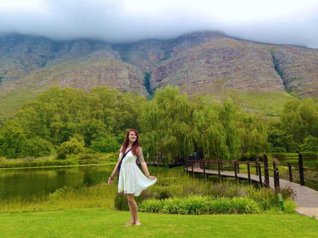 Alyssa posing in a white dress in a green field