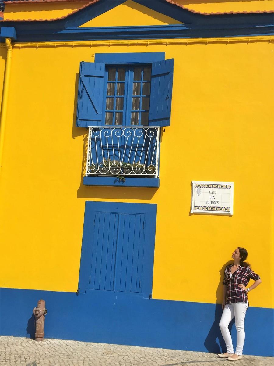 Natalia posing near a bright yellow and blue wall in Costa Nova