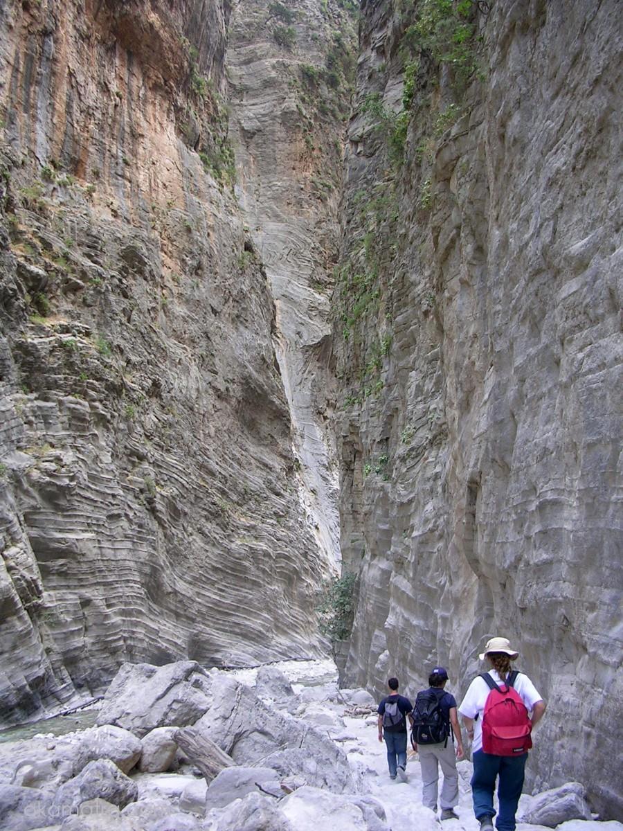 Three people walking through the narrow path of the Samaria Gorge