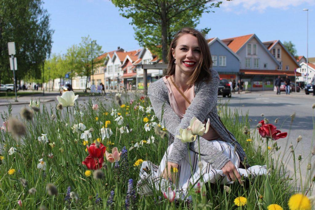 Sarah kneeling between a patch of Tulips in Norway