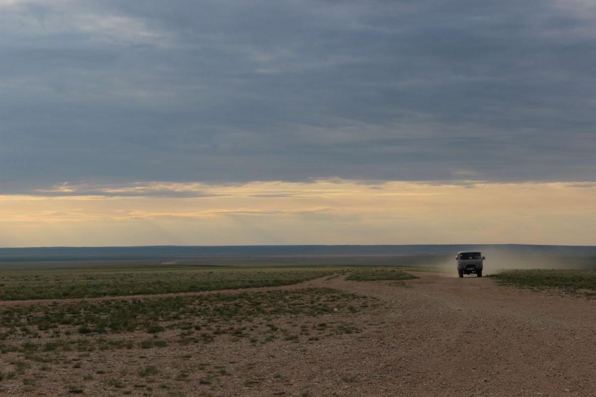 A van kicks up dust driving down a dirt road underneath a cloudy sky.