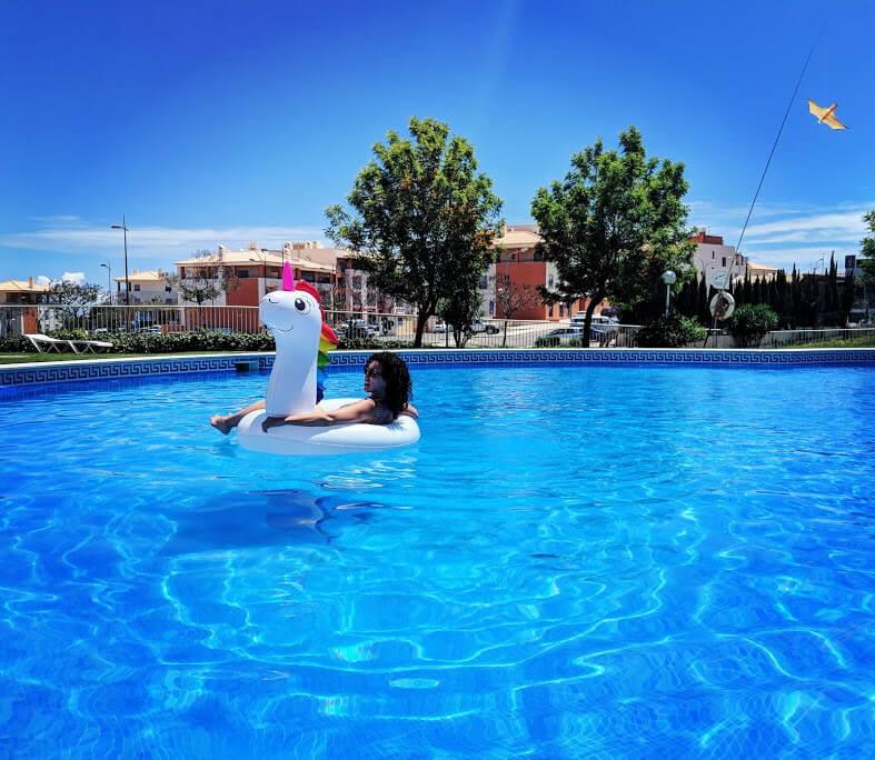 Emma floating in a unicorn floaty on a blue pool.
